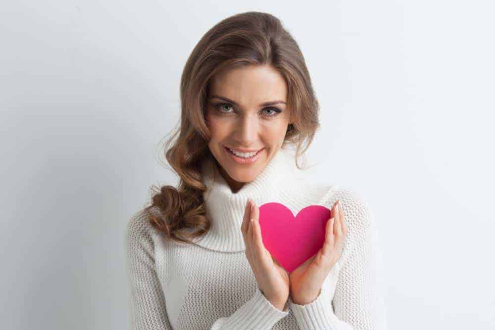 smiling woman with a paper heart representing dating